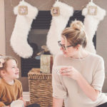 Woman and girl celebrating christmas in front of stocking